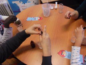 Alunos deitam gotas de corante num copo