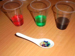 Copos com corante vermelho, verde e azul e colher com bolinhas de diferentes cores