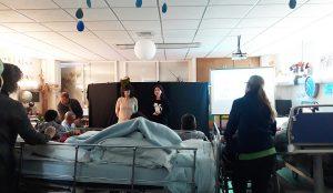 Alguns alunos em cadeira e em cama ouvem os manipuladores de marionetas