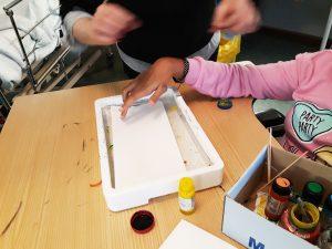 Aluna coloca papel de aguarela num tabuleiro com água
