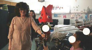 Uma mediadora cultural oferece uma marioneta, um peixe vermelho, a uma aluna