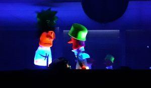 Duas marionetas de cores garridas e fluorescentes falam uma com a outra