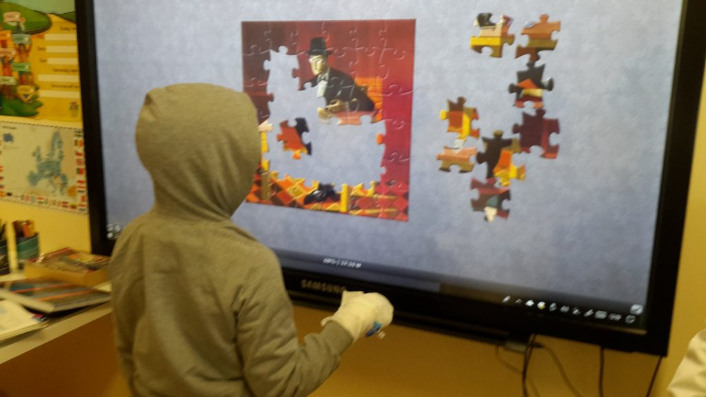 Fotografia de aluno a resolver um puzzle digital no quadro interativo