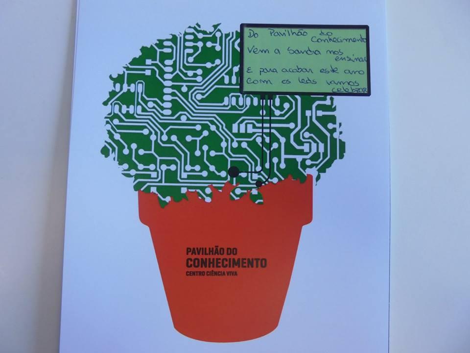 Cartão com circuito integrado em forma de manjerico e a quadra: Do Pavilhão do Conhecimento/Vem a Sandra nos ensinar/E para acabar este ano/Com os LEDs vamos celebrar