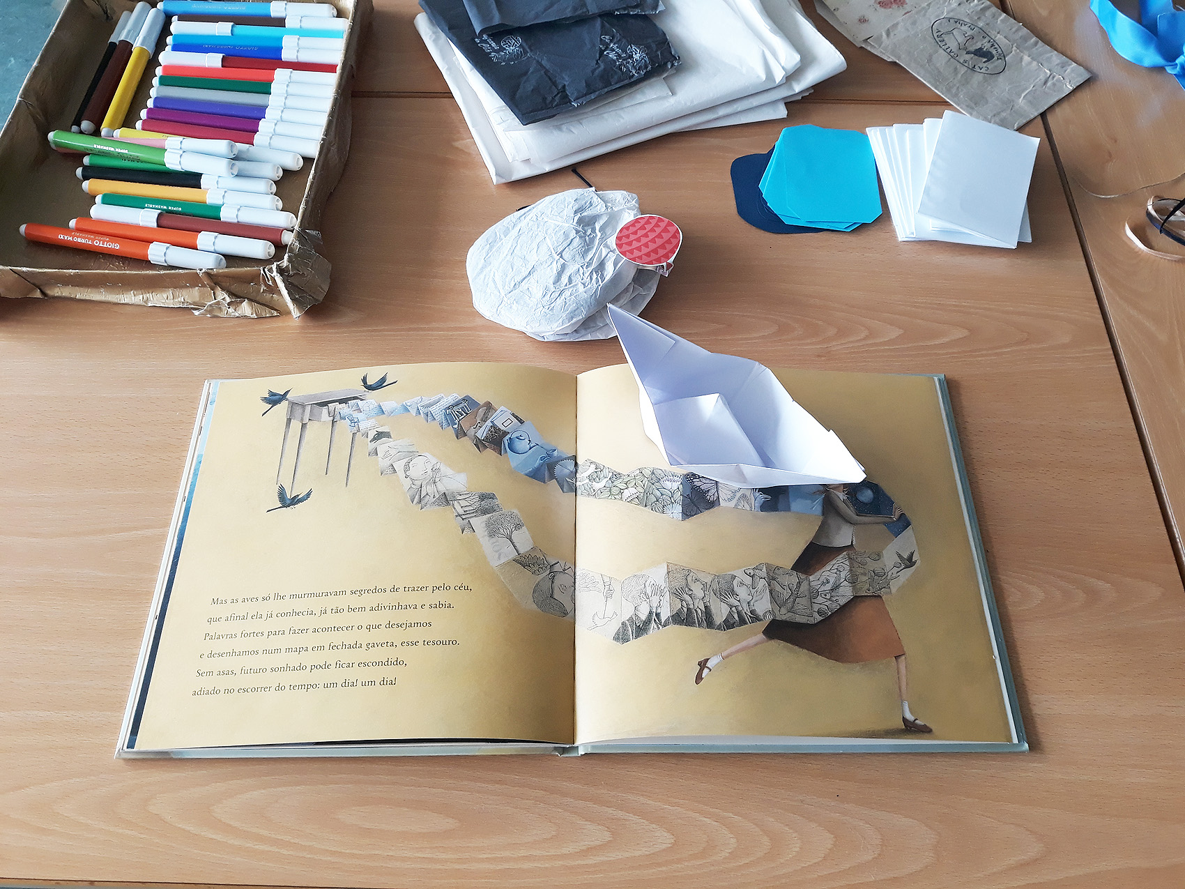 O livro aberto em cima de uma secretária com materiais de trabalho como papel de cartolinas, canetas, barco origami, um livro nuvem.