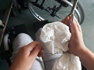 AS mãos de um aluno que segura o seu livro nuvem e o constrói com um cordel, papel e tesoura.