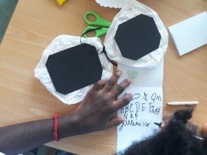 As mãos de uma aluna a escrever no seu livro nuvem.