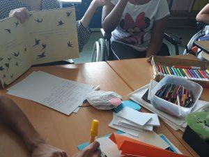 A professora segura o livro da história aberto numa página onde se veem pássaros a voar.