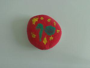Pedra pintada de vermelho com toques de amarelo e verde