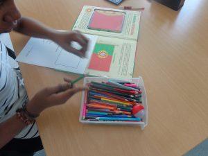 Aluno escolhe lápis de cor para pintar bandeira portuguesa