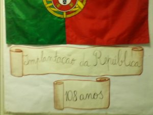 A bandeira de Portugal afixada no jornal de parede e o título Implantação da República, 108 anos.