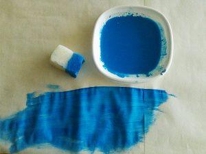 Esponja, prato com tinta azul e parte do mar pintado sobre papel de cenário.