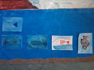 Papel de cenário azul com peixes pintados pelos alunos