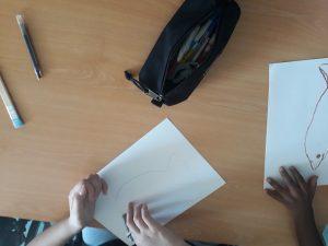 Dois alunos desenham peixes em papel para aguarela