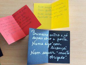 Algumas das adivinhas escritas em papel de cartolina de várias cores.