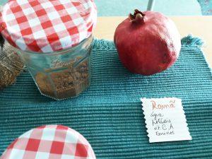 Um frasco com açúcar de coco e uma romã com a legenda acerca das características deste fruto.