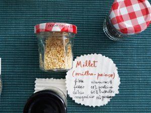 Um frasco com millet e com uma descrição das propriedades deste alimento numa rodela feita de papel. papel
