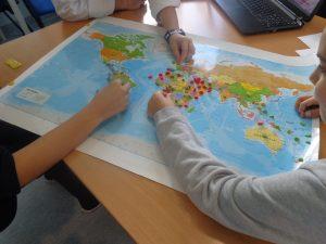 Alunos identificam regiões no mapa-mundi com marcadores coloridos