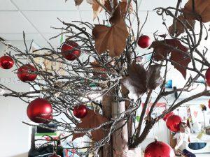 Troncos de uma árvore verdadeira e bolas vermelhas em alguns dos ramos.