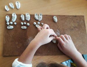 As mãos de uma aluna a moldar uma massa branca.