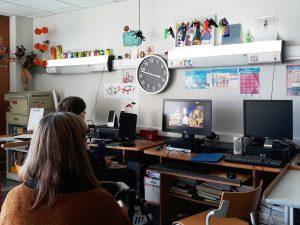 A aluna observa com atenção o vídeo onde uma das suas colegas se apresenta.