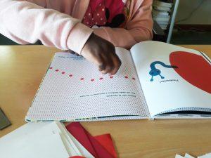 Os dedos de uma aluna sobre um percurso de círculos vermelhos que conduzem a uma lagarta.