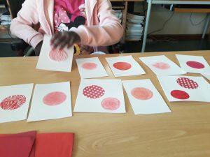 Uma aluna escolhe um de vários cartões com círculos vermelhos com diferentes texturas