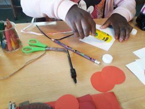 Uma aluna cola um círculo vermelho num cartão branco