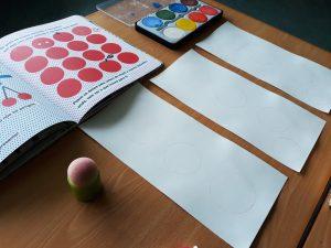 O livro aberto numa ilustração com muitos círculos vermelhos, um estojo de aguarelas coloridas e três folhas em branco