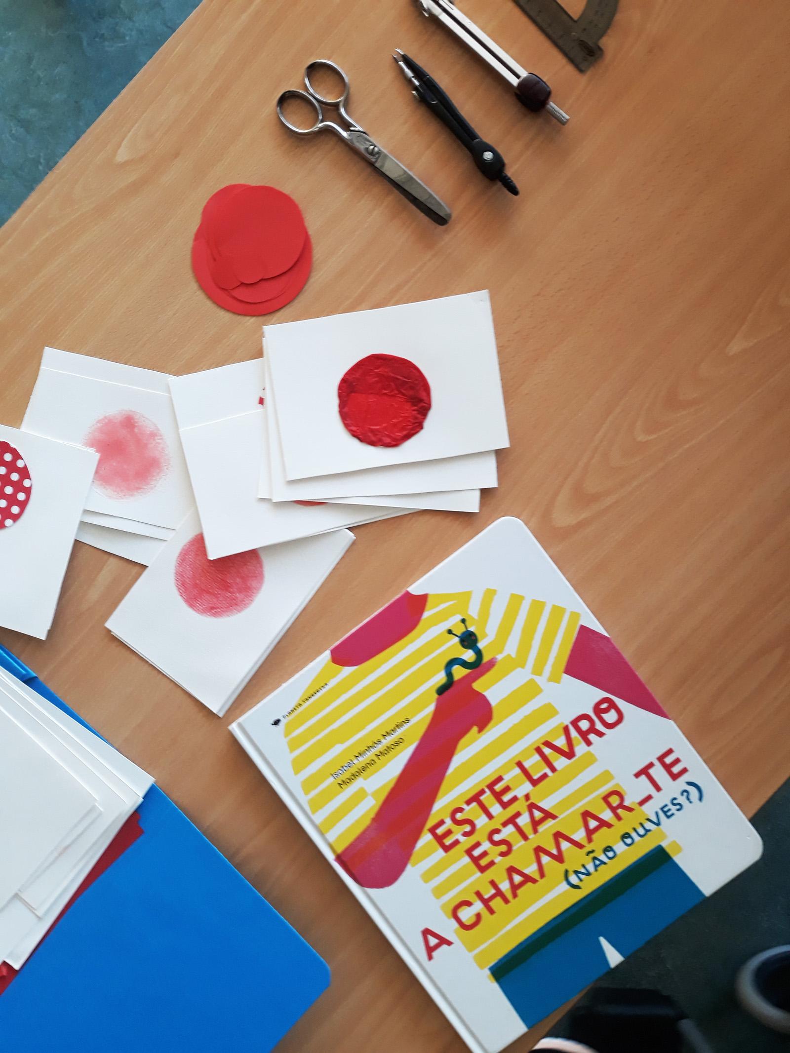 O livro fechado e vários cartões brancos com um círculo vermelho de texturas diferentes. Tesoura e compasso em cima da secretária.