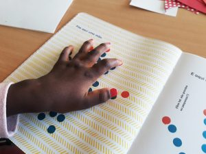 A mão de uma aluna em cima de uma página com um trajeto de círculos vermelhos e azuis