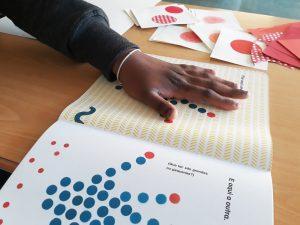 A mão de outra aluna a preencher um espaço de círculos de uma página do livro