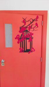 Porta da escola decorada com uma gaiola ramos e passarinhos