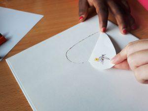 As mãos das alunas a abrirem o desenho de um coração de uma página do livro