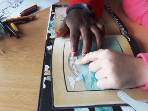 As alunas procuram imagens nas páginas do livro que se vai tornando mais claro e colorido