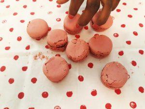 Os macarrons de morango em cima de um pano com círculos vermelhos.