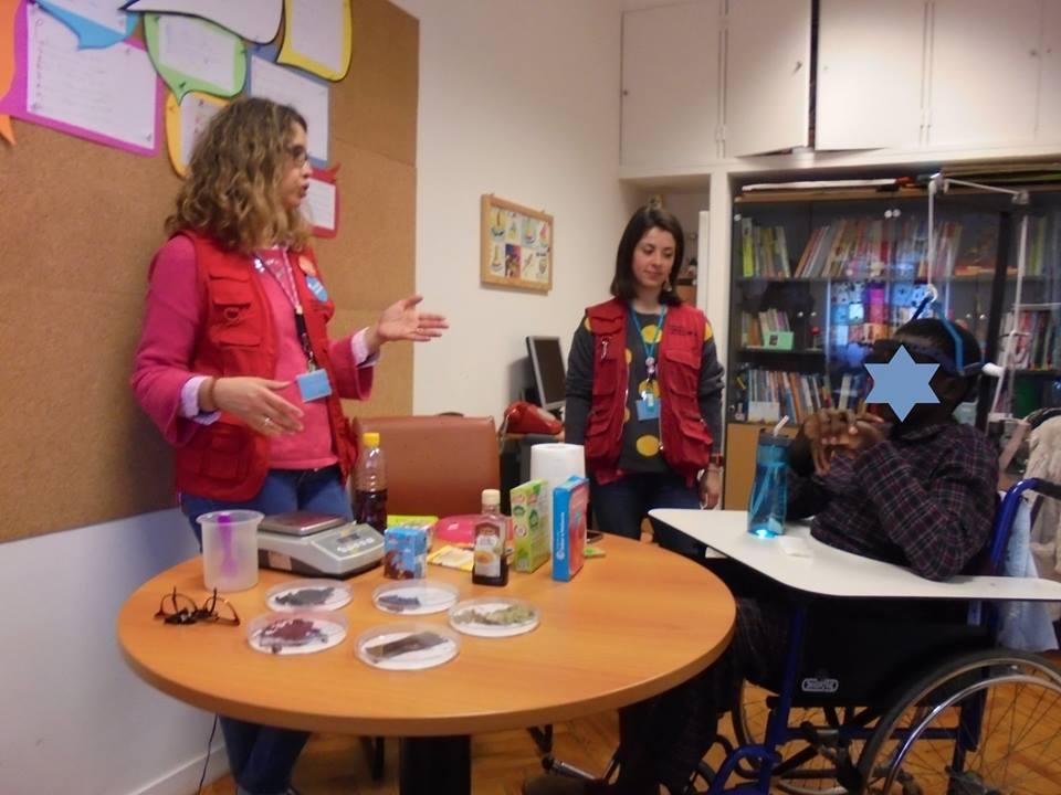 Um aluno com a Carla e Ana do Pavilhão do Conhecimento e uma mesa cheia de materiais
