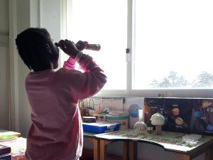 Uma aluna olha pela janela através de um óculo antigo.