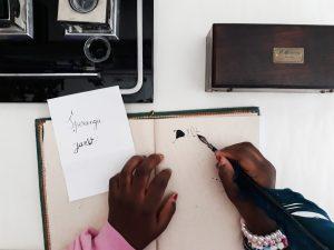 Uma aluna escreve com uma caneta antiga de pena e aparo.