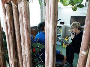 A professora lê uma história a um aluno por entre umas árvores de papel.