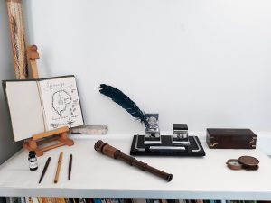 Uma mesa onde encontramos um livro aberto num cavalete, canetas antigas, um óculo, bússola e tinteiros.