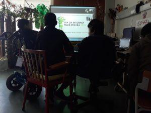Quatro jovens encontram-se à frente do quadro interativo onde está escrito Dia da internet mais segura.