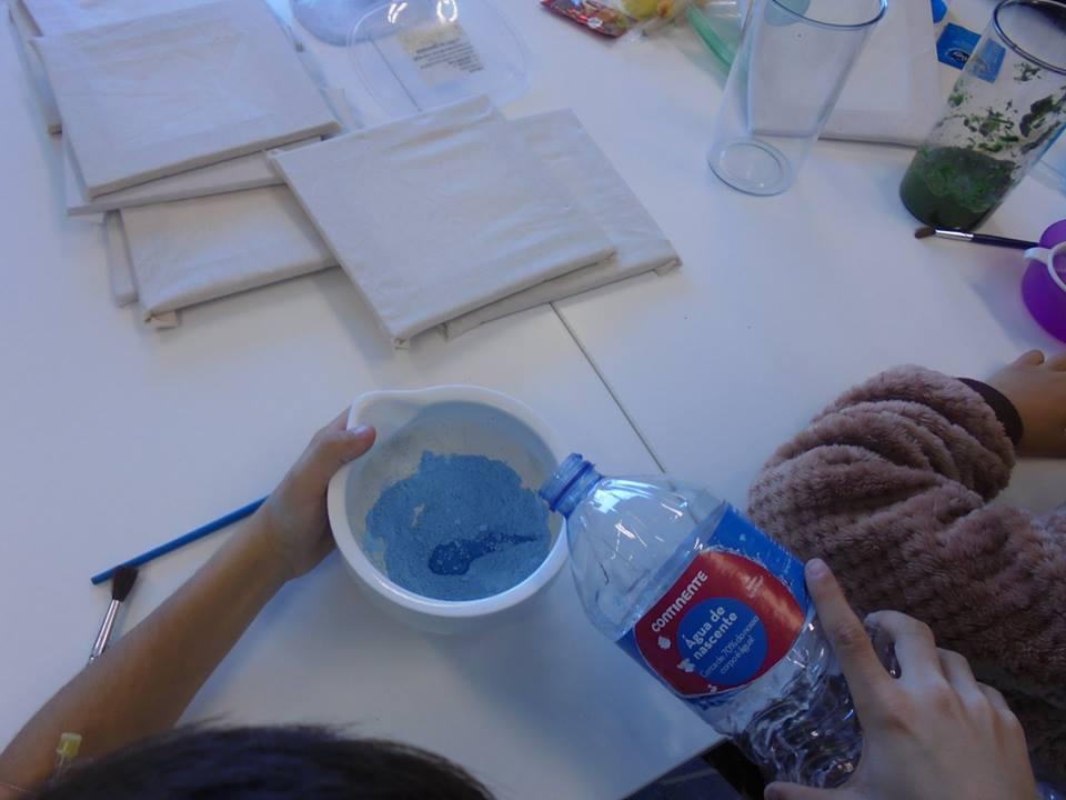 Mãos de aluno a misturar água em pasta azul