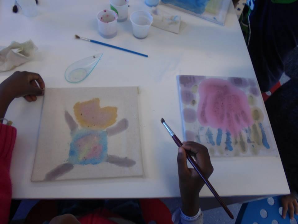Mãos de aluno com pincel e dois quadros pintados com as tintas fabricadas