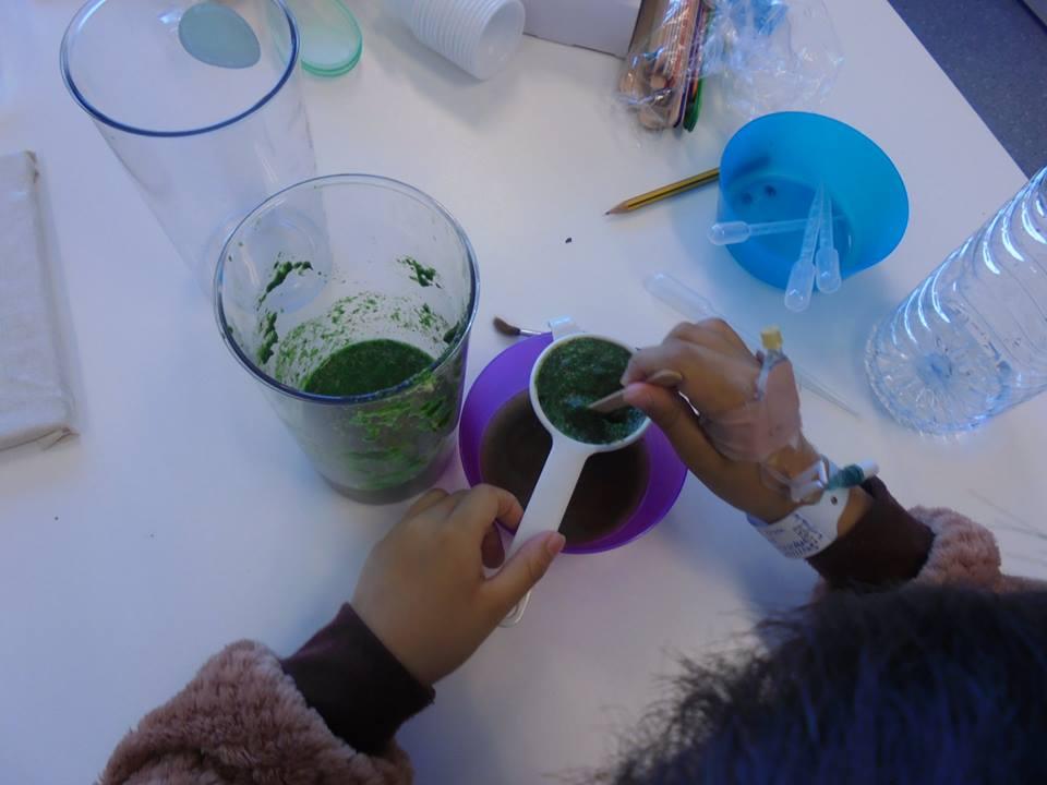 Mãos de aluna a coar pasta vegetal verde