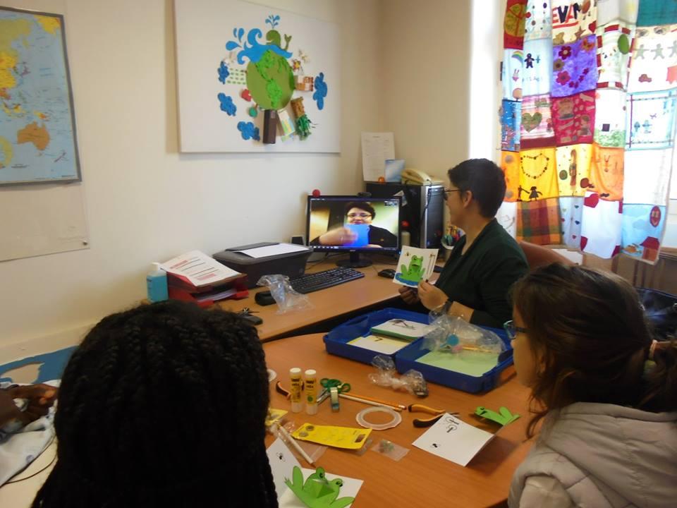Evelina (videoconferência), professora Sara a mostra um sapo em cartão e alunos