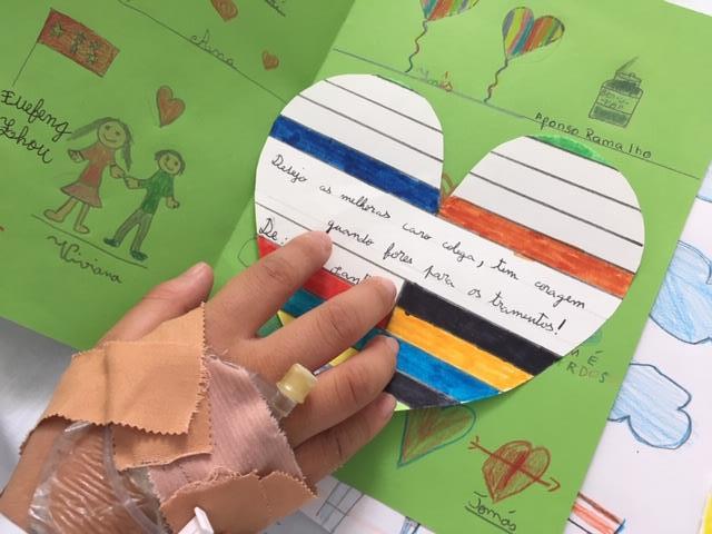Mão de aluno com cateter e postal
