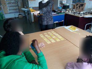 A professora faz a leitura do livro e os alunos interagem com ela.