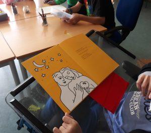 O livro em cima da prancheta da cadeira de um aluno.