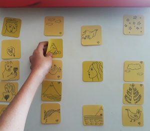 Num quadro branco, encontram-se vários quadrados com desenhos semelhantes aos do livro e um aluno retira um deles.